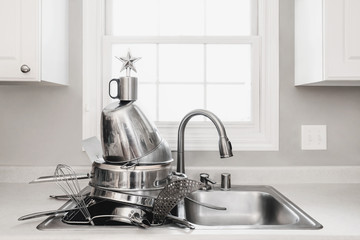 Clean stainless Steel pans in a sink with a Christmas tree star on top