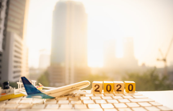 Wooden word number 2020, airplane, ship on white keyboard and blurred city scape and copy space using as background business shipping, rent container, worldwide transportation, new year concept.