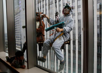 A boy looks at window cleaners, dressed as a rat and a wild boar, this year and next year's Chinese zodiac animals, cleaning the windows of Ryumeikan hotel during a promotional event to celebrate the upcoming new year in Tokyo