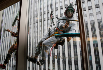 A window cleaner dressed as a rat, one of next year's Chinese zodiac animals, cleans the windows of Ryumeikan hotel during a promotional event to celebrate the upcoming new year in Tokyo