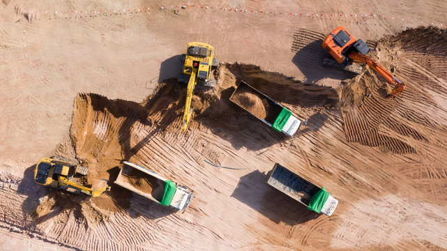 Aerial view group of excavator and dump truck working on a construction site, Construction site view from above.