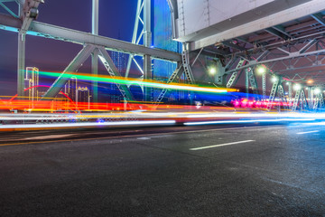 Fotomurales - car light trails on steel bridge with city skyline.