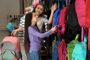 Little school girl with mother choosing backpack in supermarket