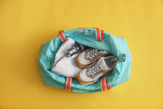 Gym bag with sports equipment on yellow background, top view