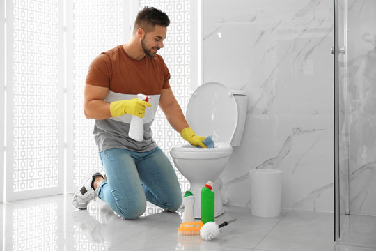 Young man cleaning toilet bowl in bathroom