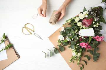 Florist making beautiful bouquet at white wooden table, top view Wall mural