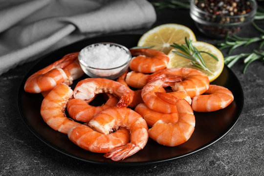 Delicious cooked shrimps with salt and lemon on dark grey table