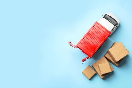 Top view of toy truck with boxes on blue background. Logistics and wholesale concept