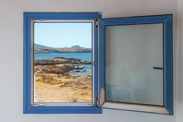 Old wooden blue window with the view of the beach in the background