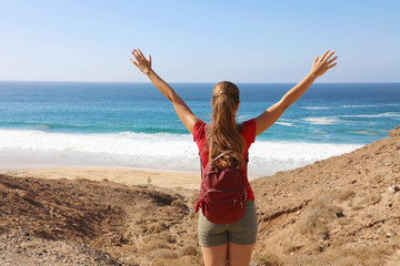 Photo sur Aluminium Iles Canaries Reaching goal. Female hiker backpacker arrives at the Atlantic Ocean after a long way and celebrating with arms up.