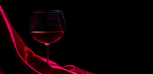 Spoed Foto op Canvas Wijn Glass of red wine on red silk against black background. Wine list design background.