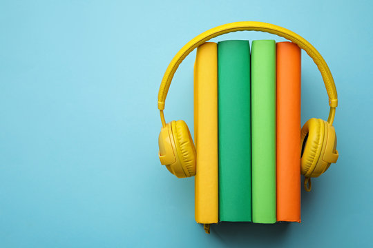 Books and modern headphones on light blue background, top view. Space for text