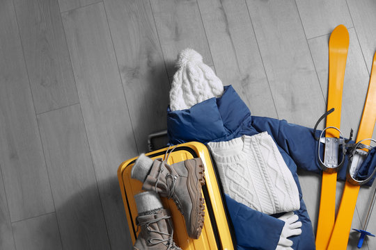 Suitcase with warm clothes and skis on wooden floor, flat lay. Winter vacation