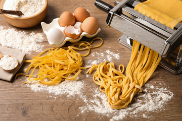 Fototapeta Pasta maker machine with dough and products on wooden table, above view obraz