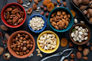 Variety of different types of nuts - almonds, pine nuts, pastachio, cashew, pecan and hazelnuts- in bowls. Overhead view