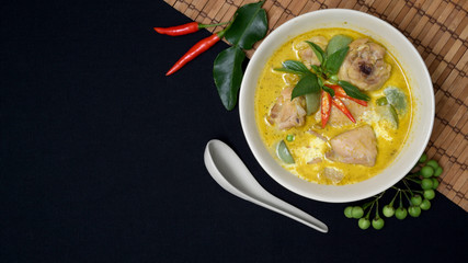 Chicken green curry and ingredients on black desk background with copy space