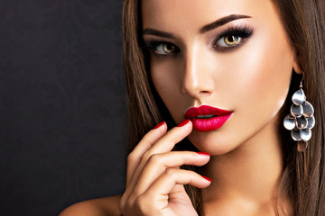 seductive woman with dark brown eye makeup and bright red lips and nails Wall mural