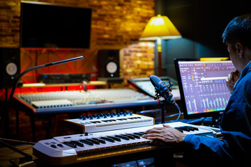 professional male music producer arranging a song on computer in recording studio. music production concept
