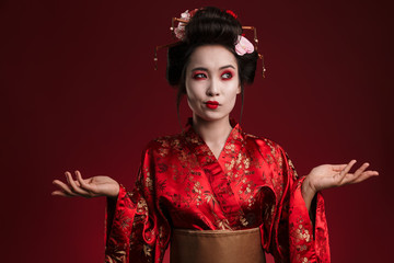 Image of beautiful young geisha woman in traditional japanese kimono hesitating