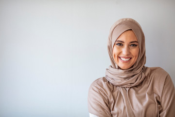 Portrait of pretty young asian muslim woman in head scarf smile. Portrait closeup of muslim prayer woman 20s in hijab smiling isolated over gray background.