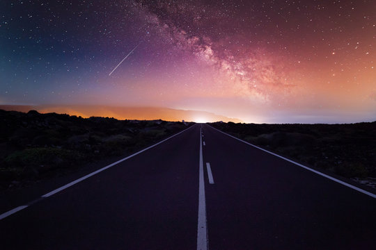 Highway and starry night sky with milky way in desert