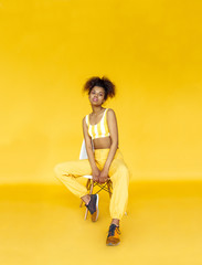 Fashion young african girl black woman wear stylish yellow clothes looking at camera sit on chair isolated on studio wall background, vertical banner for website design, portrait, copy space