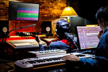 professional male music producer, composer working with guitarist in recording studio. music production concept