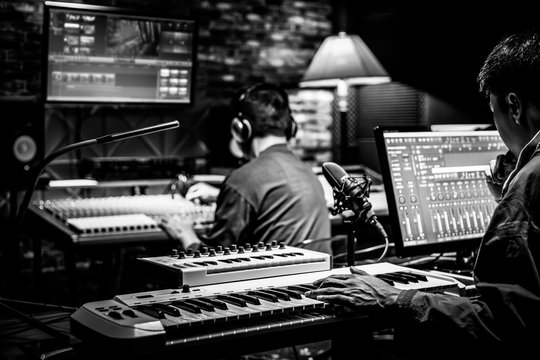 professional male producer, director, editor, composer working with sound engineer in recording studio. music production concept
