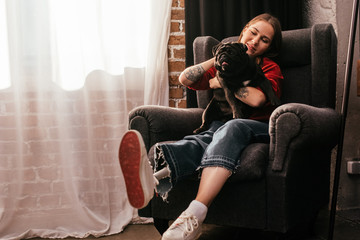 Smiling young woman with leg prosthesis playing with pug in armchair at home