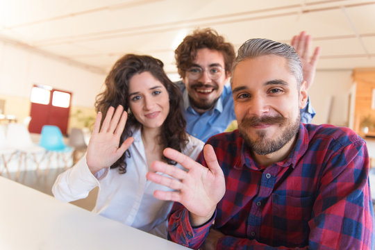Portrait of happy successful creative team waving hello. Business colleagues in casual meeting in contemporary office space, looking at camera, smiling. Team portrait concept