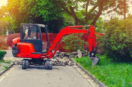 Small excavator on sidewalk near lawn. Repair in city, urban