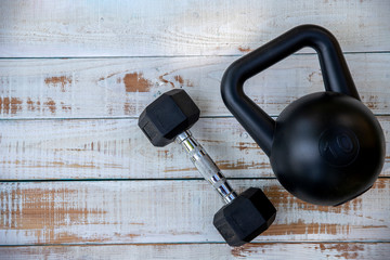 exercise weight, dumbbell, kettle bell on white wooden background