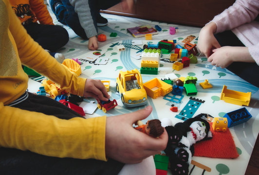 London, UK / December 15 2019: Kids playing with Duplo building blocks toys on a play mat