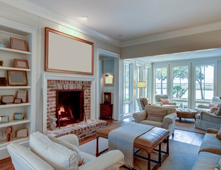 Beautiful living room with fireplace and blank picture frame. Place your own artwork over the mantle.