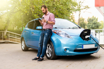 Young handsome man use phone and drink coffee while his electro car charging at station.