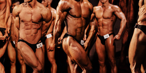 group of athletes bodybuilders posing triceps arms in bodybuilding competition