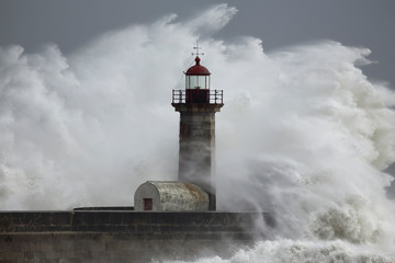 Stormy dramatic wave over lighthouse