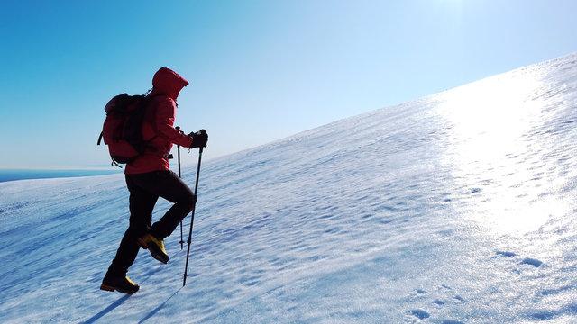 Mountaineer climbs a snowy mountain over blue clear sky. Winter