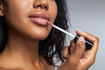 Pretty calm lady applying lip gloss in studio