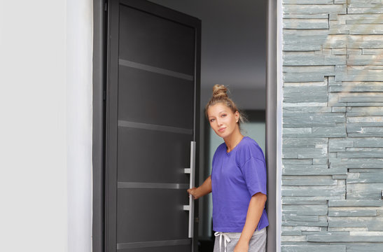 Beautiful woman opening the door of her home.Inviting the guests