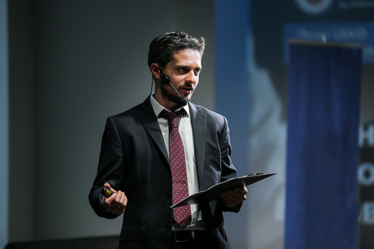 Attractive and confident successful man with headset speaking at corporate business coaching and training conference.Business and Entrepreneurship event,motivation training