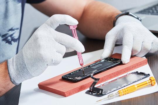 smart phone repair. repairman hands with screwdriver