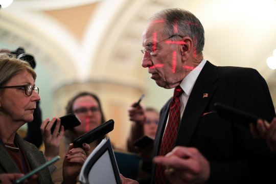 U.S. Senator Grassley is illuminated by beams of light from another camera's flash as he speaks to reporters at the U.S. Capitol in Washington