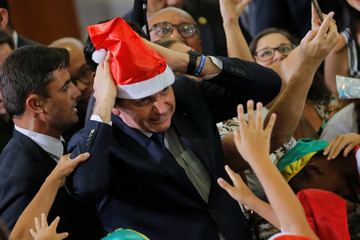 Brazil's President Jair Bolsonaro poses for a picture wearing a Santa Claus hat during  a Christmas ceremony at Planalto Palace in Brasilia