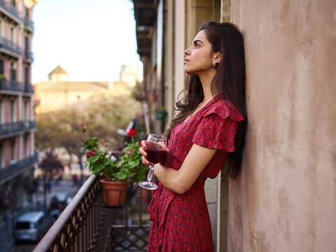 Young lady with wine on balcony
