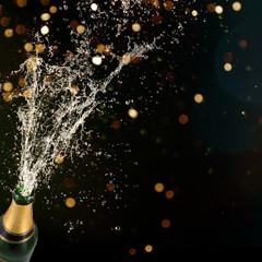 Bottle of champagne with splashing liquid, New year or other celebration theme.