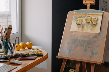 Easel with unfinished drawing of yellow apples in the studio