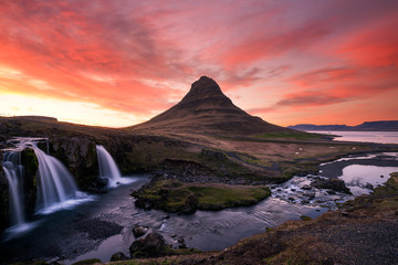 Fototapeten Koralle Pink skies over the famous kirkjufellsfoss waterfall in the icelandic landscape during sunset. Traveling and landscapes concept.