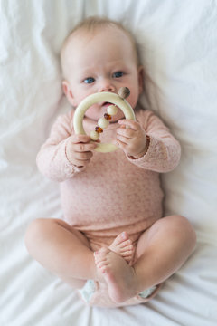 Baby girl playing with her toys and feet