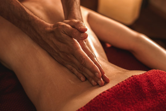 Alternative Medicine. Therapist healing woman doing abhyanga back massage with herbal oil hands on spine close-up